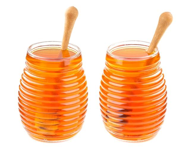 Miele in barattolo di vetro isolato su fondo bianco