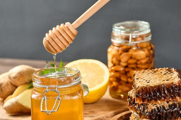Miele in favi su un piatto di legno e miele dorato in un barattolo con noci e pettine per miele con limone e zenzero