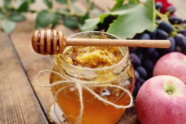 Miele in un bellissimo vaso, mandrino cucchiaio di legno, uva e mele su un fondo di legno