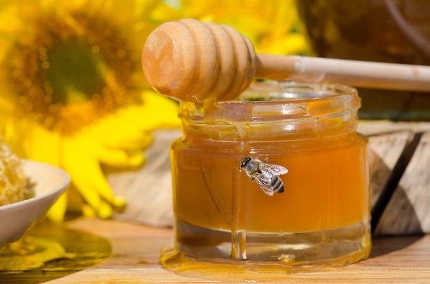 Miele in vasetti di vetro e ape occidentale. ape. ape che si siede sul bicchiere di miele. miele in barattolo di vetro con ape volante