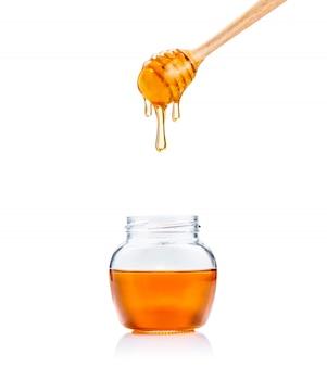 Miele in vasetto di vetro e mestolo di miele di miele con miele che gocciola giù, il tutto su sfondo bianco