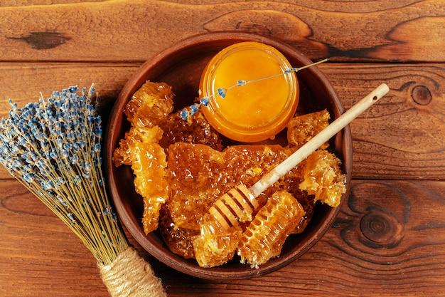 Miele in vaso con merlo acquaiolo del miele su fondo di legno dell'annata