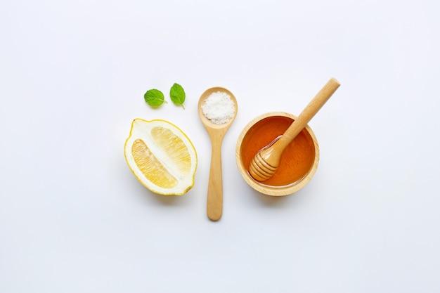Miele, limone, menta e sale su sfondo bianco.