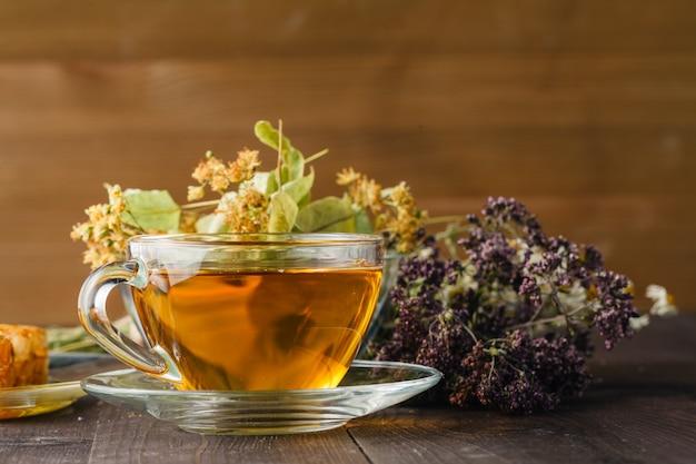 Miele liquido con nido d'ape e tazza di tè all'interno del mazzo di erbe secche su superficie di legno bianco