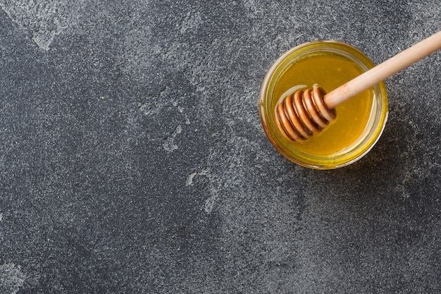 Miele liquido e bastoncino di miele su una superficie grigia.