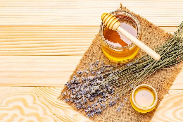 Miele liquido fresco in barattoli di vetro con un mestolo di miele in legno