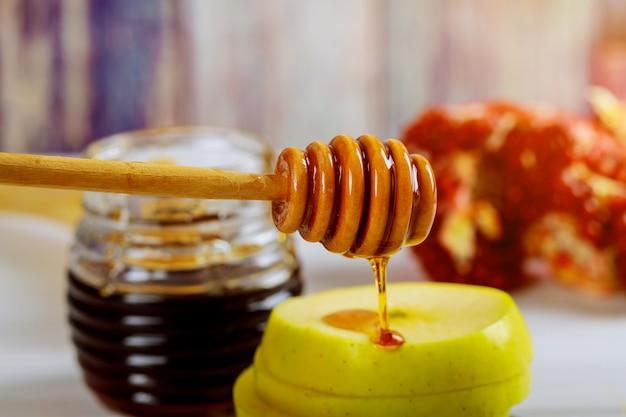 Miele, mela e melograno sulla tavola di legno sopra il fondo del bokeh