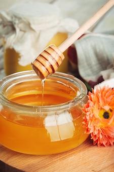 Miele. miele dolce in barattolo di vetro su di legno.