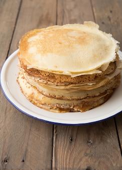 Miele o sciroppo d'acero che versa sopra le crepes. vista del primo piano della pila di pancake sottili, blini