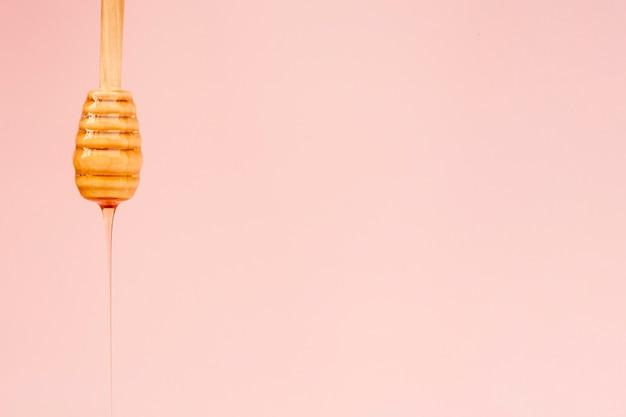 Miele saporito del primo piano che versa dal bastone