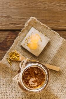Miele; semi di polline d'api e caramelle sul panno del sacco