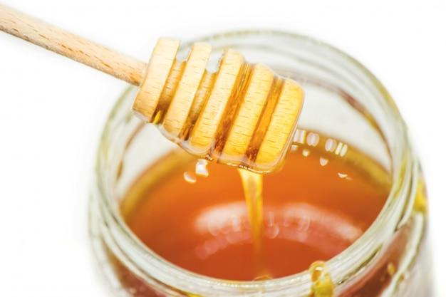 Miele su uno sfondo bianco. messa a fuoco selettiva. cibo.