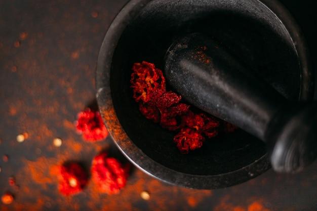 Mietitore di carolina secco piccante rosso e polvere in mortaio di pietra. foto scura