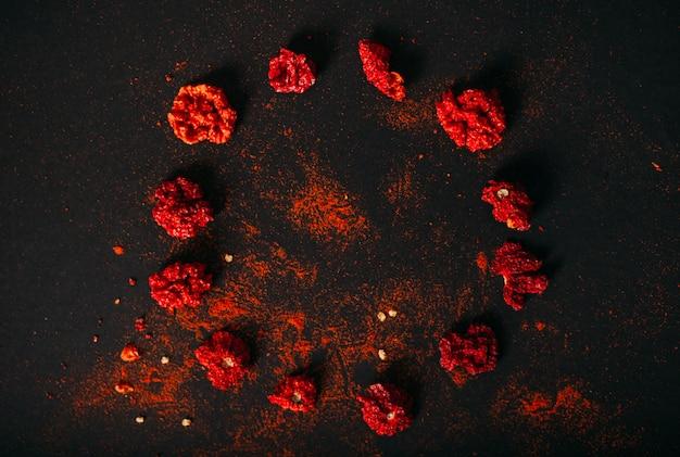 Mietitore rosso secco piccante della carolina. fotografia di cibi scuri. copia spazio.