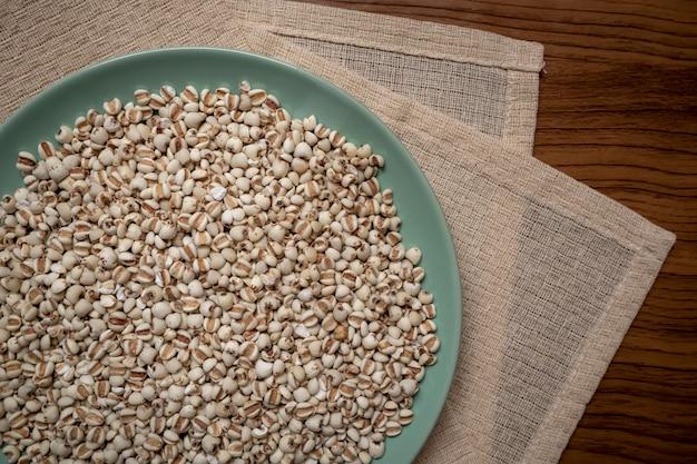 Miglio in un piatto verde che è cereali e cibo su una tovaglia marrone, venature del legno, adatto per la pubblicità alimentare