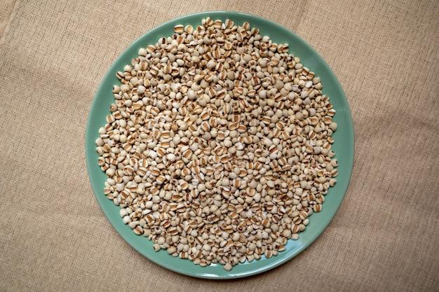 Miglio in un piatto verde che è cereali e cibo su una tovaglia marrone, venature del legno