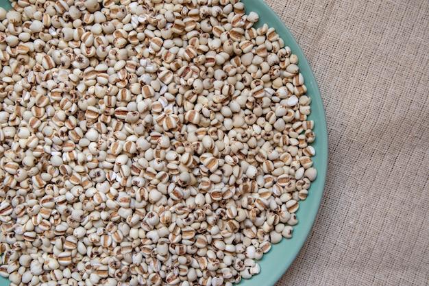 Miglio in un piatto verde che è cereali e cibo su una tovaglia marrone,