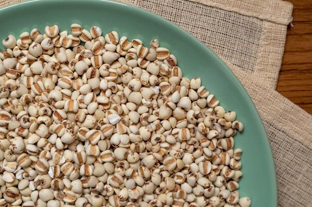 Miglio in un piatto verde che è cereali e cibo su una tovaglia marrone.