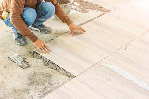 Miglioramento domestico, rinnovamento - il piastrellista del muratore sta piastrellando