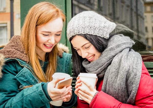 Migliore amico delle amiche felici divertendosi con la tazza asportabile del caffè nella stagione invernale