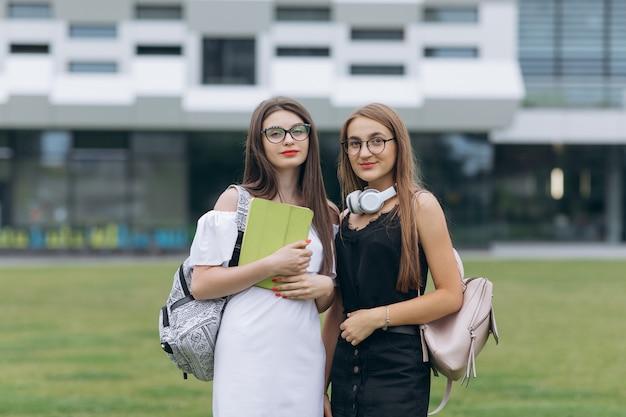 Migliori amiche caucasiche delle giovani donne divertendosi indossando gli occhiali da sole d'avanguardia, posare all'aperto