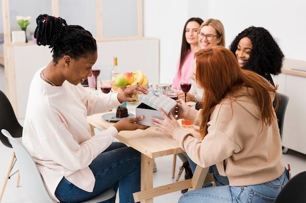 Migliori amiche che scambiano regali durante una riunione