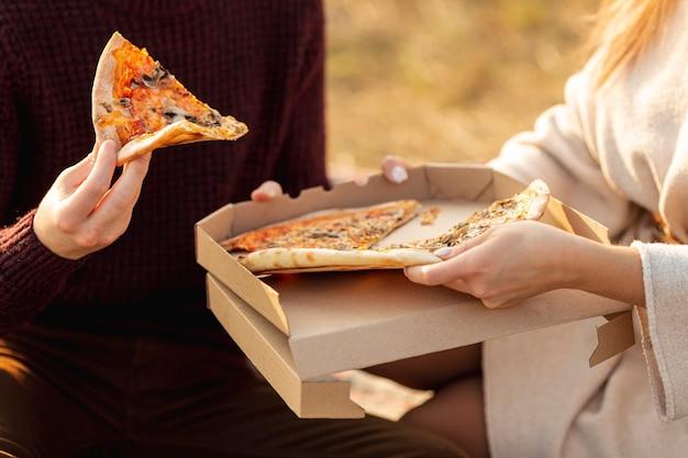 Migliori amiche che si godono una pizza insieme fuori dal primo piano