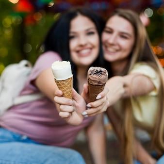 Migliori amiche del colpo medio che posano con il gelato