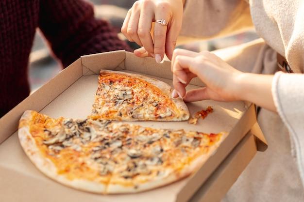 Migliori amiche dell'angolo alto che godono insieme di una pizza fuori