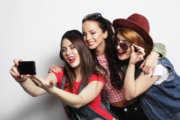 Migliori amiche delle ragazze dei pantaloni a vita bassa che prendono selfie