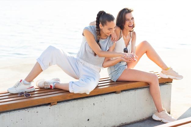 Migliori amici a distanza che giocano su una panchina