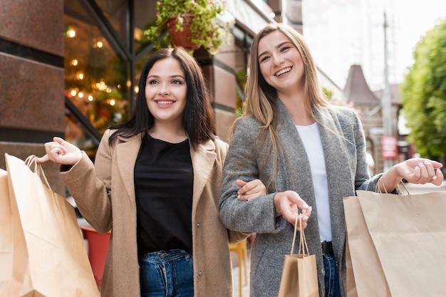 Migliori amici che tengono le borse della spesa all'esterno