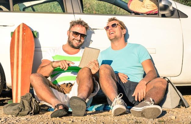 Migliori amici dei giovani pantaloni a vita bassa divertendosi con la compressa durante il roadtrip dell'automobile