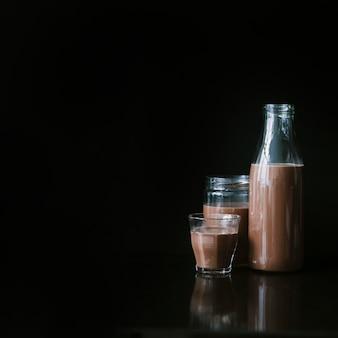 Milk shake al cioccolato in vetro; barattolo e bottiglia su sfondo nero