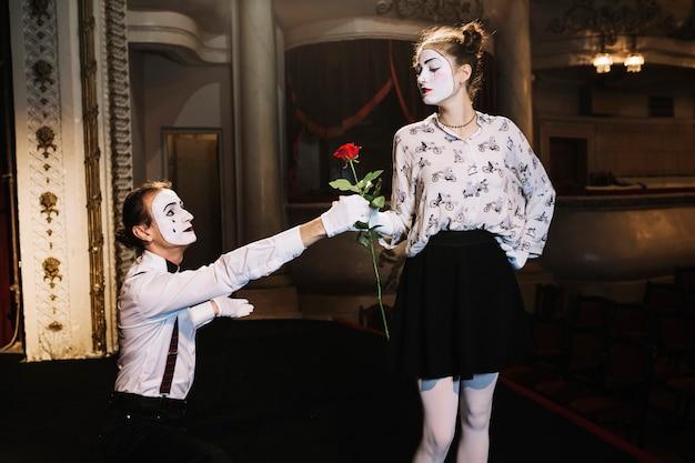Mime maschio che dà rosa rossa all'artista femminile del mimo in scena
