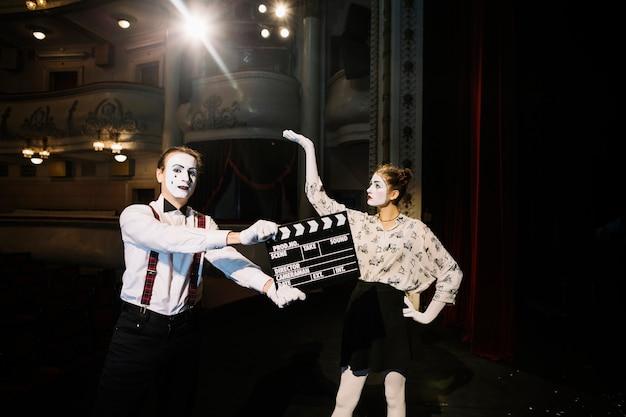 Mimo maschio artista in piedi davanti al mimo femminile artista sul palco
