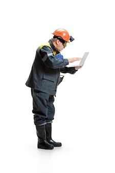 Minatore maschio barbuto senior pensieroso che sta nella vista di profilo alla macchina fotografica con il computer portatile su un bianco