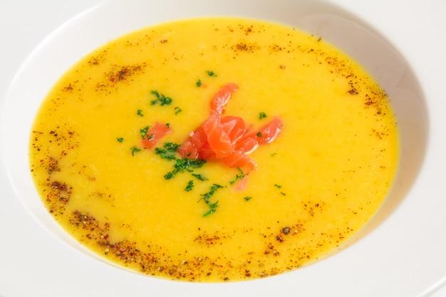 Minestra arancio del primo piano in un piatto bianco