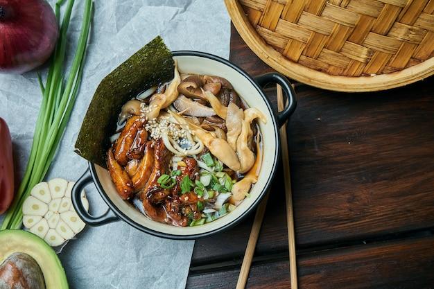 Minestra asiatica classica con tagliatelle di udon, nori, funghi shiitake e pollo fritto in una ciotola nera sulla tavola di legno con lo spazio della copia. vista dall'alto, cibo piatto laico
