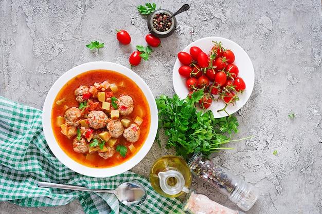 Minestra calda del pomodoro dello stufato con il primo piano delle verdure e delle polpette in una ciotola sulla tavola. zuppa di albondigas, cibo spagnolo e messicano. vista dall'alto. disteso