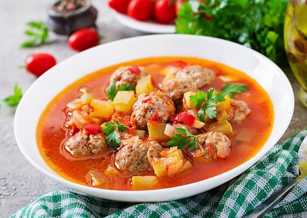 Minestra calda del pomodoro dello stufato con il primo piano delle verdure e delle polpette in una ciotola sulla tavola. zuppa di albondigas, cibo spagnolo e messicano.