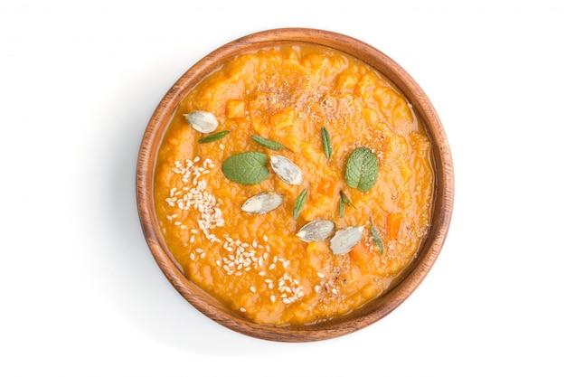 Minestra crema di patate dolci o batata con semi di sesamo in una ciotola di legno isolata su uno sfondo bianco. vista dall'alto.
