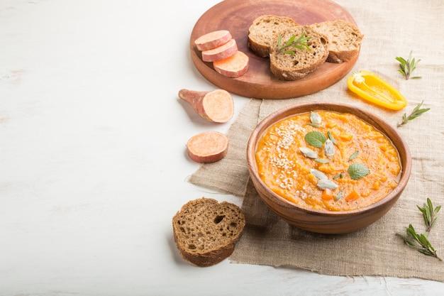 Minestra crema di patate dolci o batata con semi di sesamo in una ciotola di legno su un fondo di legno bianco. vista laterale, copia spazio.