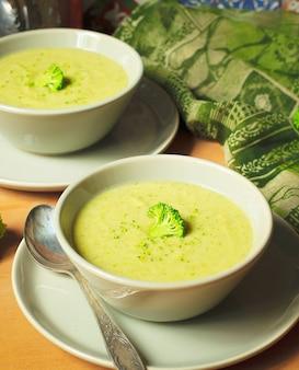 Minestra crema fresca dei broccoli su due ciotola ceramica grigia sul piatto con il cucchiaio su fondo di marmo.