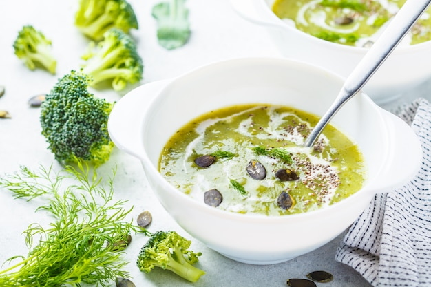 Minestra della crema dei broccoli della disintossicazione del vegano con i semi di zucca e della crema della noce di cocco in ciotola bianca, spazio della copia.