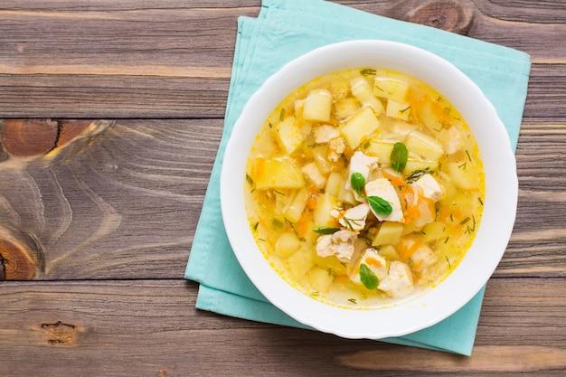 Minestra di brodo di pollo fresca con patate ed erbe in una ciotola bianca sul tovagliolo sulla tavola di legno.