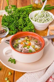 Minestra di pollo con i piselli e le verdure in una ciotola su un fondo di legno