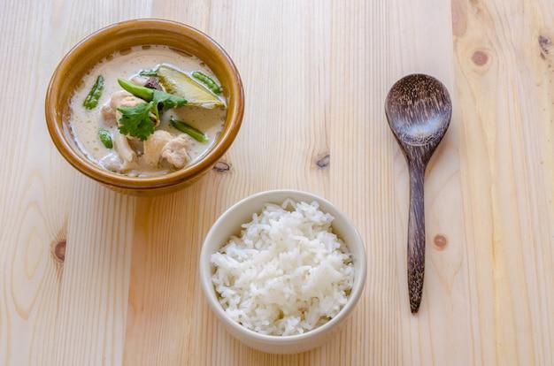 Minestra di pollo tailandese in latte di cocco (tom kha gai) con riso su fondo di legno, alimento tailandese.