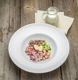 Minestra fredda del yogurt di estate con il ravanello, il cetriolo e l'aneto sulla tavola di legno. okroshka russa.
