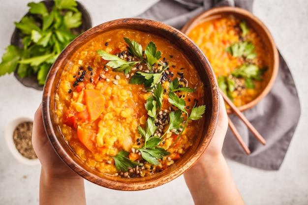 Minestra indiana gialla della lenticchia del vimine curry con prezzemolo e sesamo in una ciotola di legno in mani.